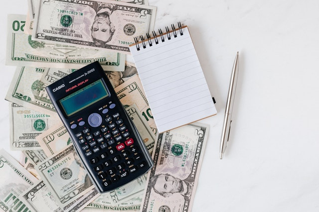 Calculator on a table next to the pile of money