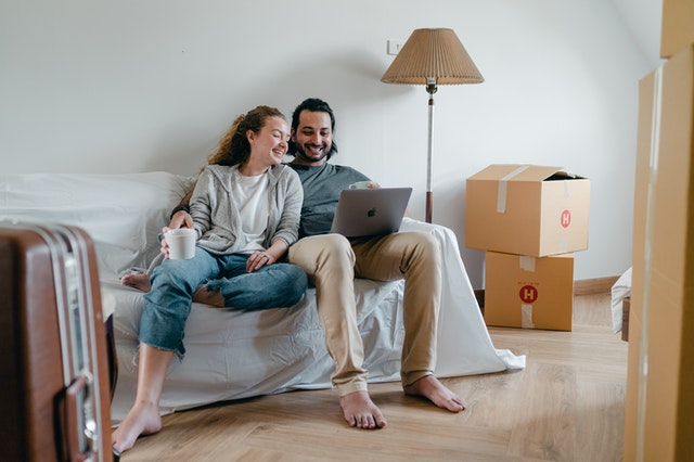 Man and a woman sitting on a sofa surrounded by moving boxes