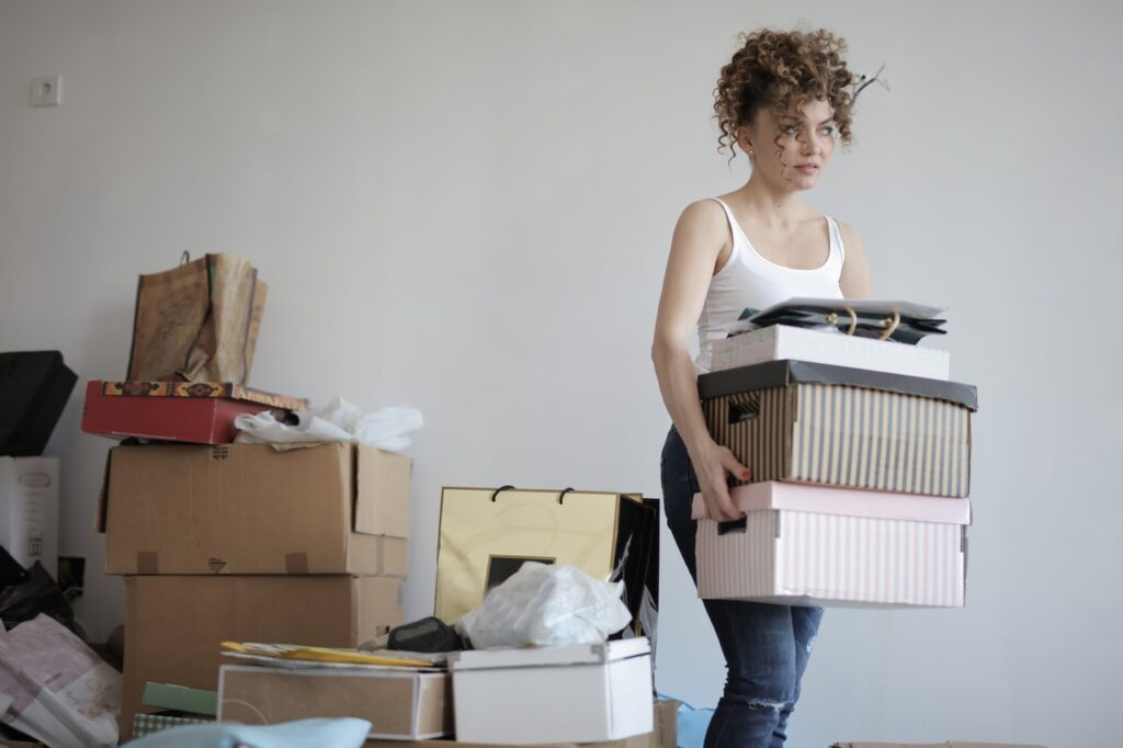 a woman carrying cardboard boxes outside of a room with clutter
