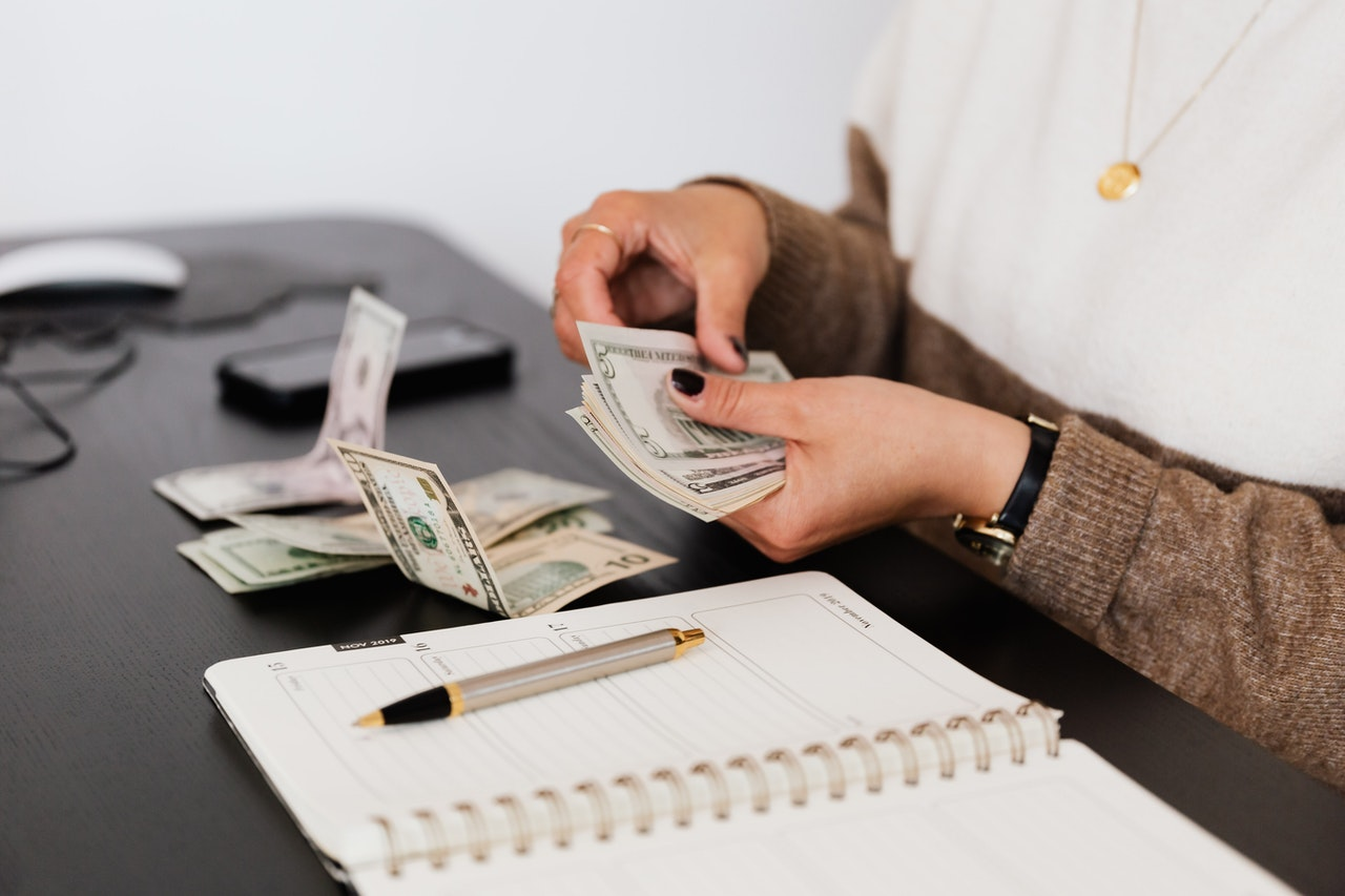 a woman counting money after calculating something at the table