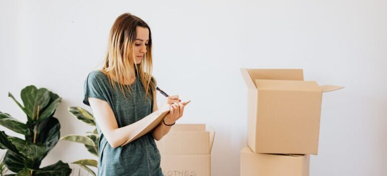 A woman writing down notes while packing