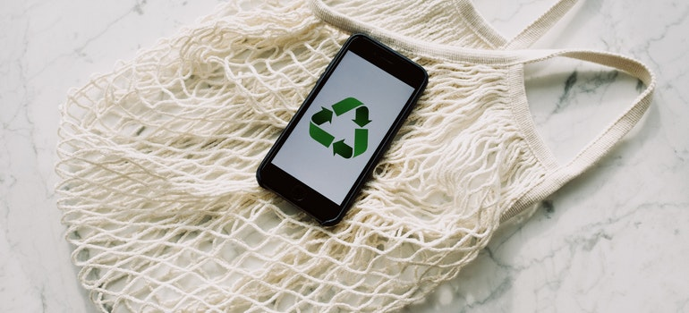 Recycle sign on phone wallpaper and mesh bag