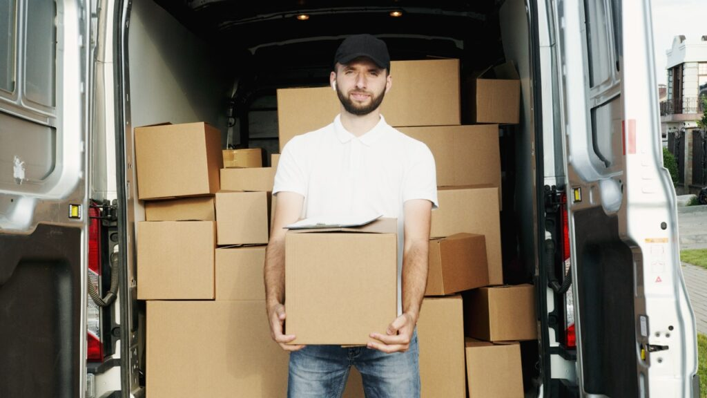A man holding a box in front of a moving truck