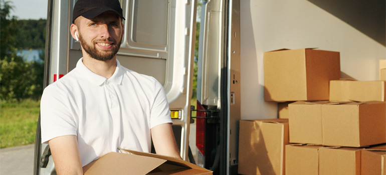 A professional mover holding a box in front of a truck, representing cross country moving companies Illinois