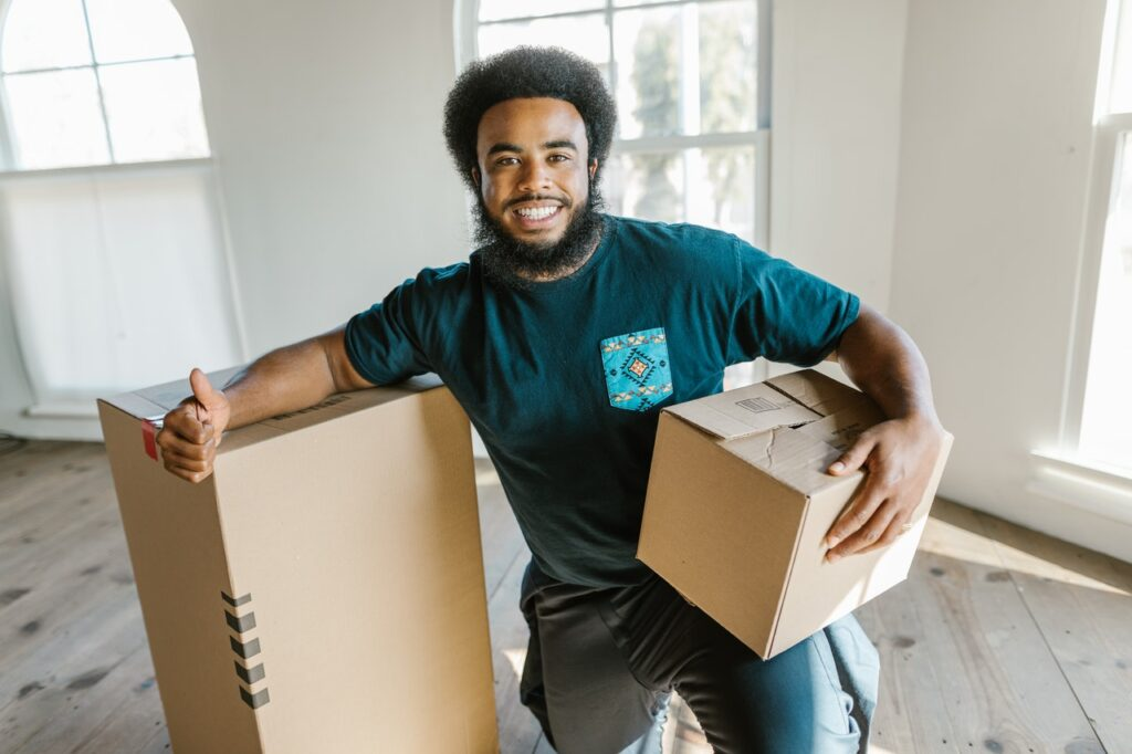 A professional mover holding a box and showing a thumbs up