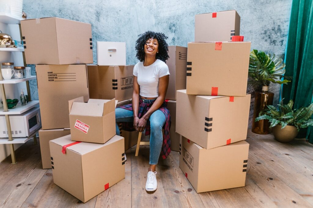 A woman sitting among boxes, smiling.