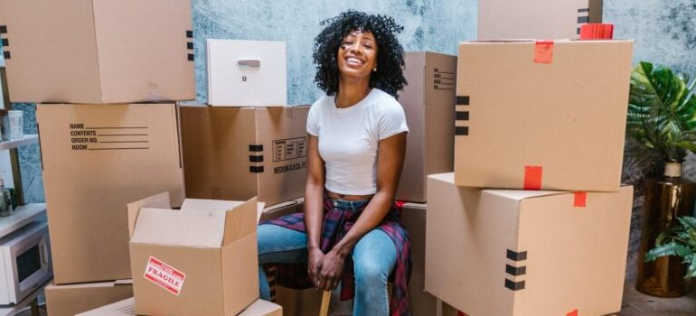 person sitting amidst cardboard moving boxes