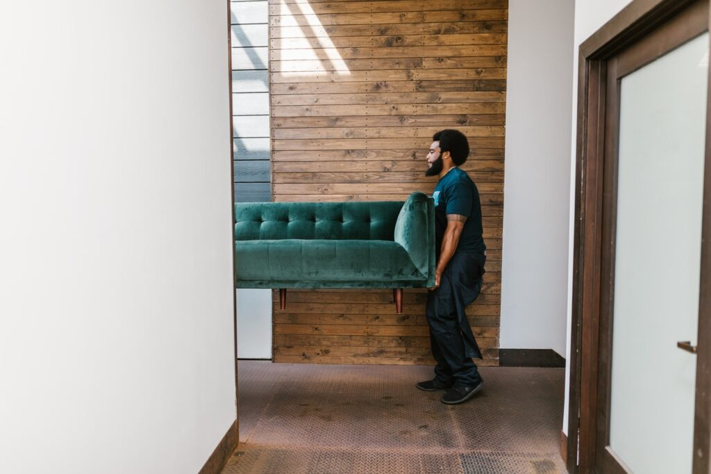 A man carrying a couch