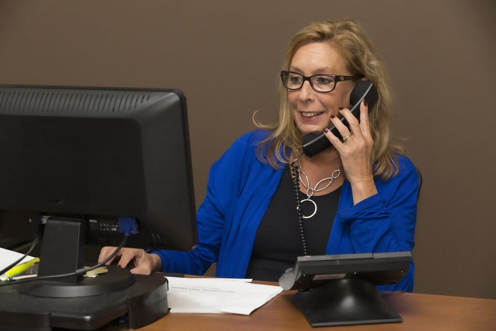 A woman working behind a computer, speaking on the phone