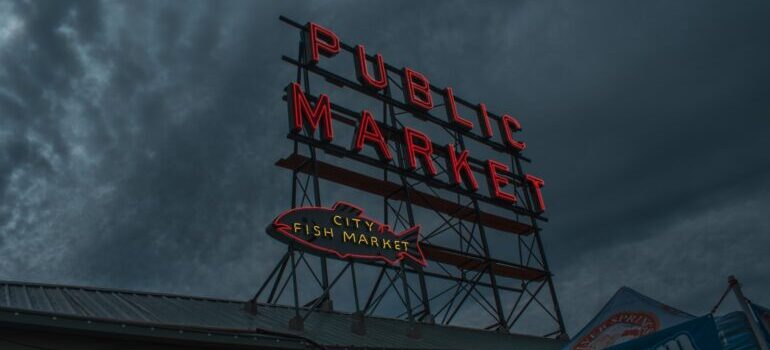 red public market sign in seattle with the clouds in the background