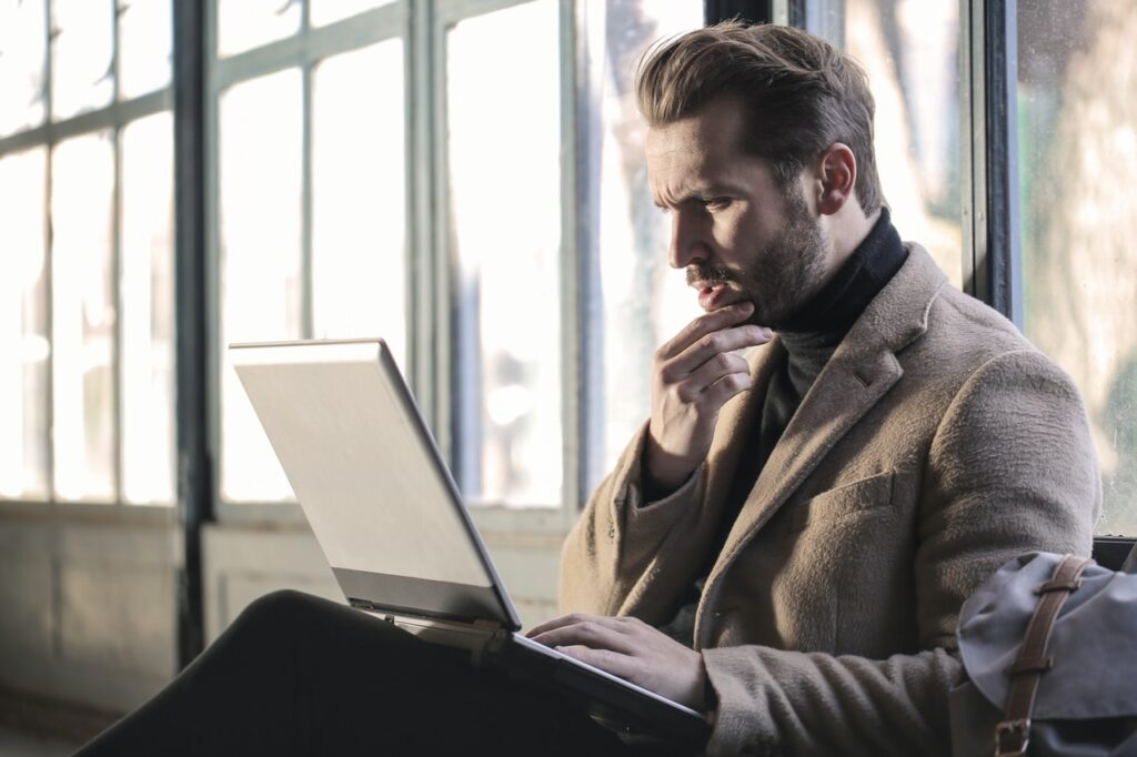A man reading something on his laptop, looking rather intrigued