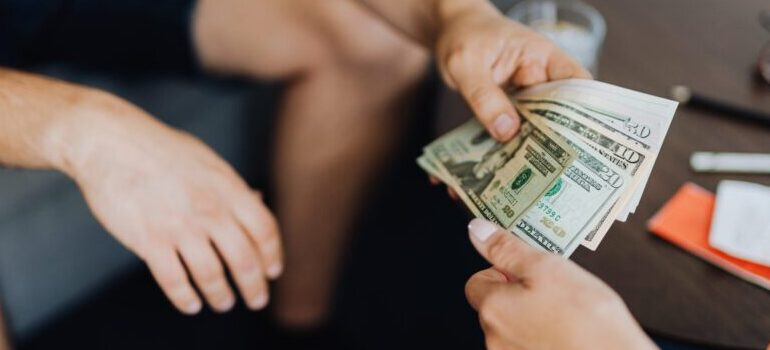 person giving money to another person