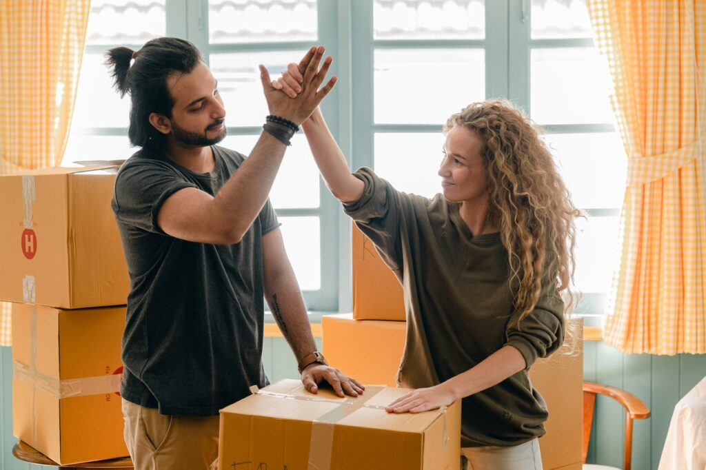 A man and a woman throwing a high-five over packed boxes