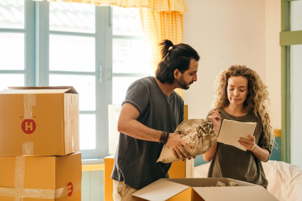 A man and a woman packing and making a list