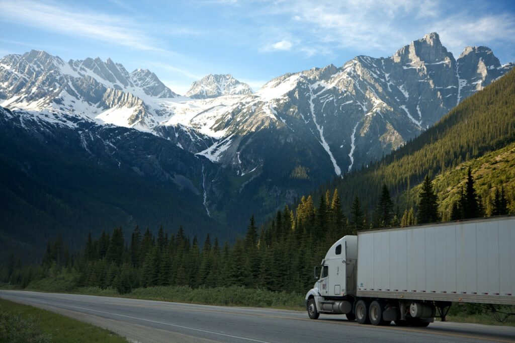 A moving truck on a highway with mountains in the background