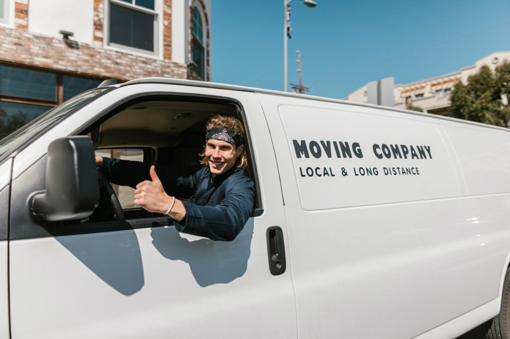 A mover showing a thumbs up from his van