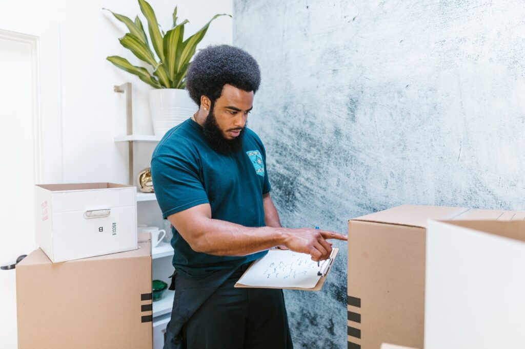 A mover checking whether the box is properly labeled