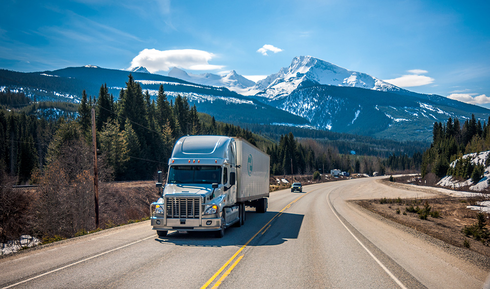 A moving truck on a highway with gorgeous scenery in the back