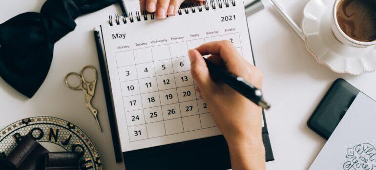 A pwrson writing in a calendar.