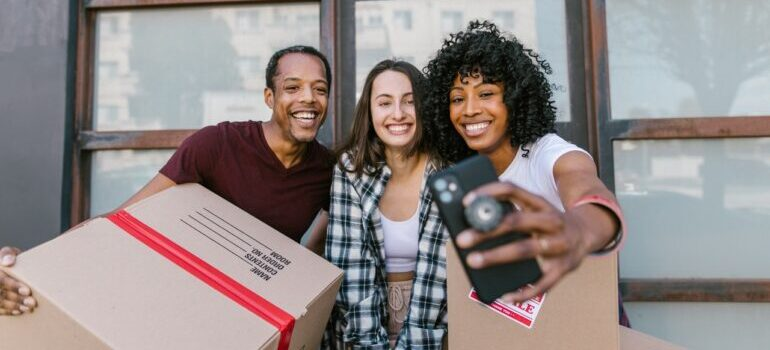 A woman taking a selfie with friends who helped her organize a DIY move.