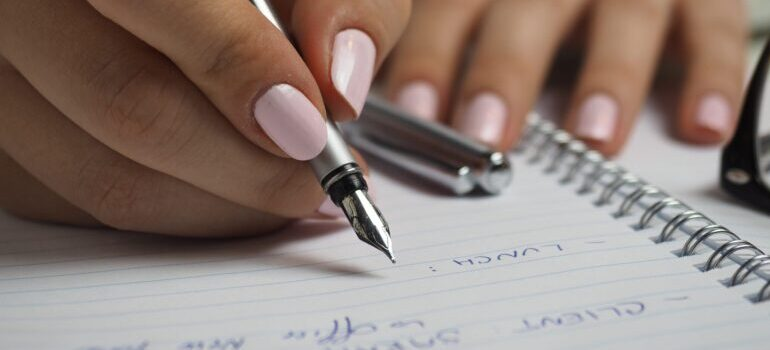person writing a checklist, symbolizing your part in the moving process