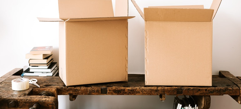 used moving boxes on a table that can help you save money on a long-distance move