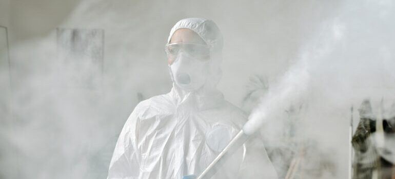 A person wearing a protection suit spraying a hazardous matter.