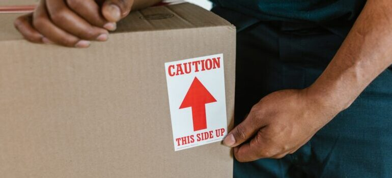 person carrying a box with a label on it