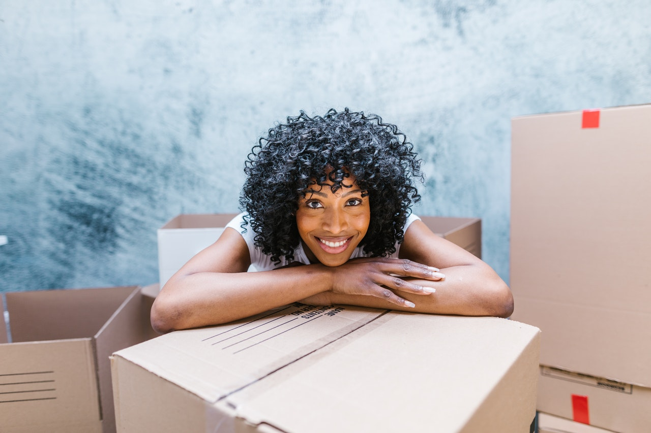 A woman leaning over a box, smiling