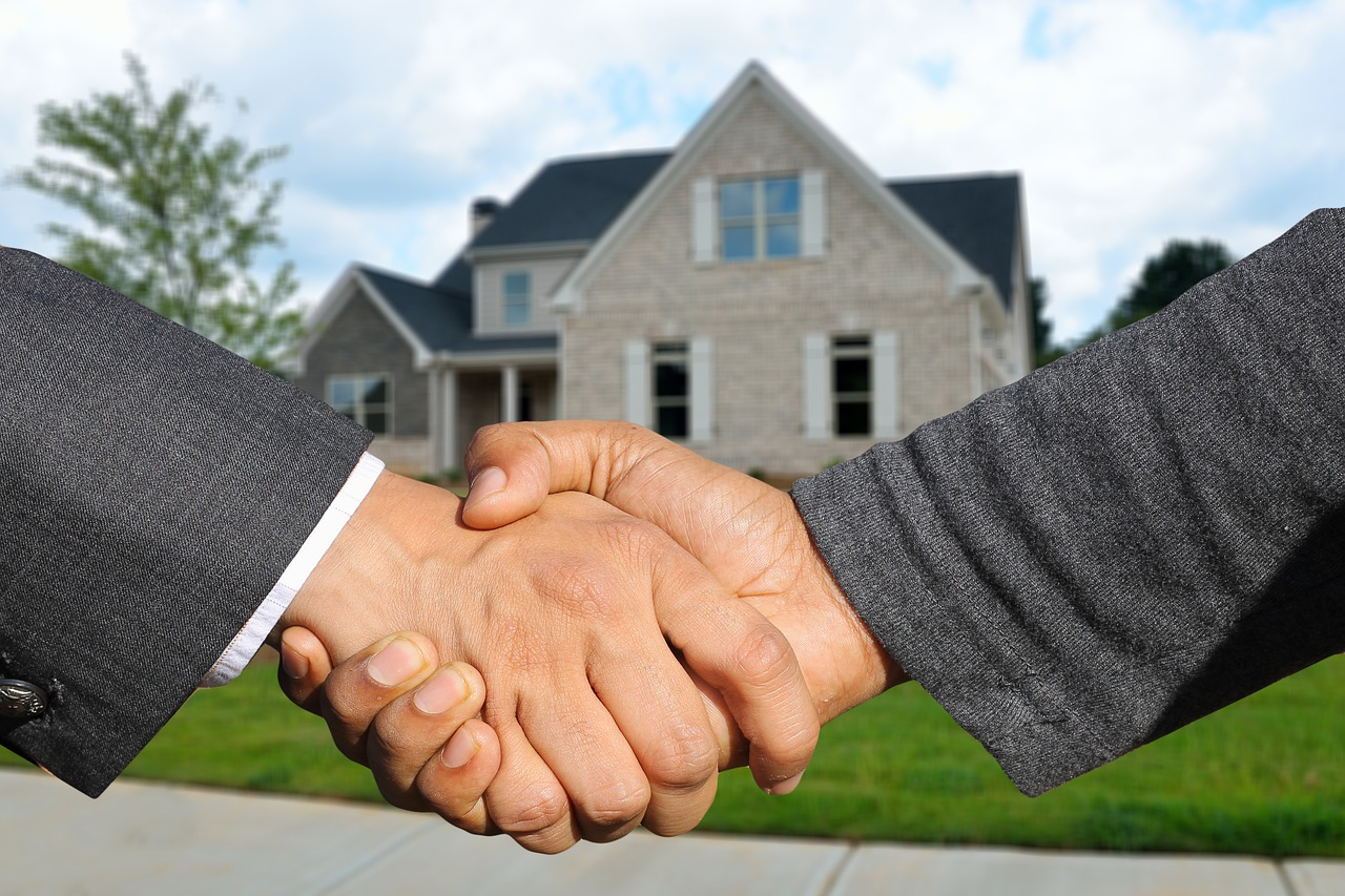 two men in suits shaking hands in front of a house